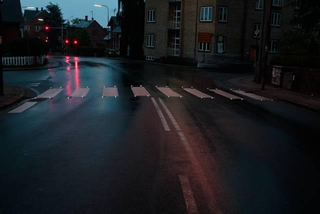"""Mindst 73% af personskadeuheldene og dødsulykkerne sker når en fodgænger er i færd med at krydse kørebaner, cykelstier eller i kryds. Alle ved, at et fodgængerfelt eller en fodgængerovergang markerer en overgang på vejen, hvor bilerne og anden trafik skal holde tilbage for eventuelle fodgængere, der ønsker at kommer over vejen. Fodgængerfeltet kan så markeres overfor bilisterne ved hjælp af et blåt skilt – visse steder suppleres med gule lamper. Disse forholdsregler er kendt i gadebilledet, derfor sker det ofte at en bilist overser en fodgænger. LED-Mark ITS har udviklet et system, som gør det mere sikkert både for den krydsende fodgænger og bilisten. Orange solcellebrikker integreres i de hvide """"zebrastriber"""" i fodgængerfeltet, som kun aktiveres, når nogen krydser feltet. På den måde advares bilisten kun i det øjeblik, der er en fodgænger. Kan styres fra et lyssignal i forbindelse med et kryds. Systemet består af en kombination af I-Module og LED-Guides."""